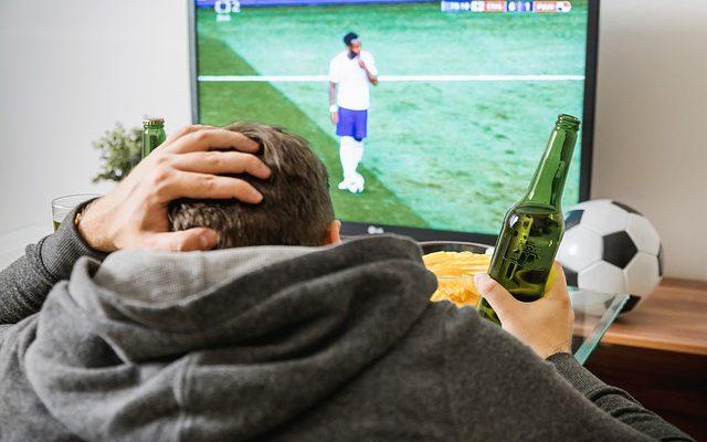 Homem assistindo jogo da equipe nacional na tv